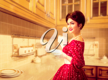 Attractive pinup girl with make-up drinks coffee on the kitchen cafe, 50 american fashion. Red dress with polka dots, vintage style