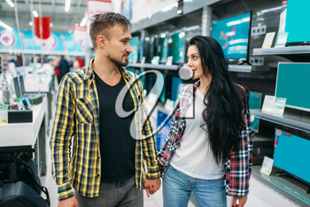 Young couple choosing electric iron in supermarket. Male and female customers on family shopping. Man and woman purchasing goods for the house