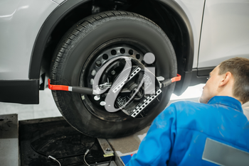Mechanic adjusts the target on collapse of convergence stand in auto-service. Computer diagnostic of car suspension