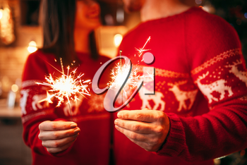 Love couple holds sparklers in hands, christmas romantic celebration. Man and woman celebrate xmas together
