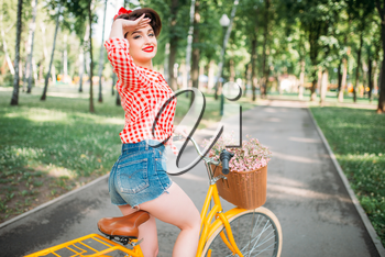 Pinup girl on retro bicycle with backet of flowers. Pin-up style pretty woman