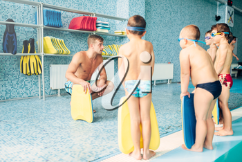 Instructor training children in the pool, view from back. Boys with swimming goggles and planks for swimming stands near water. Sportive kids activity in modern sport center with pool.