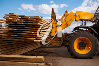 Forklift loads the boards in the lumber yard outdoor. Autoloader works on timber mill warehouse, woodworking industry, carpentry. Wood processing on factory, forest sawing, sawmill