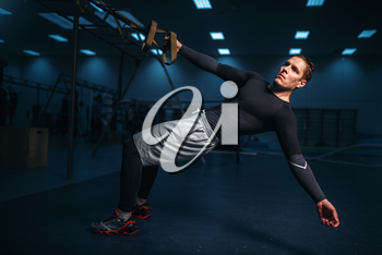 Male athlete on training, stretch workout with ropes in gym. Energy exercises in sport club