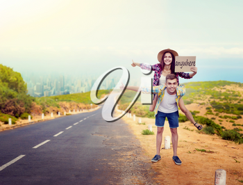 Hitchhiking couple holds blank cardboard, happy hitchhikers travels anywhere. Hitchhike adventure of young man and woman