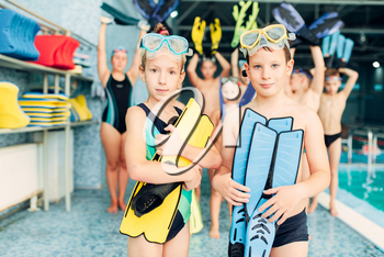 Portrait of boy and girl with colorful flippers in hands near swimming pool. Sportive healthy children after swimming exercises. Happy kids in modern sport center.
