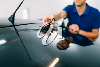 Male worker with scissors, car tinting film installation process, tinted auto glass installing procedure