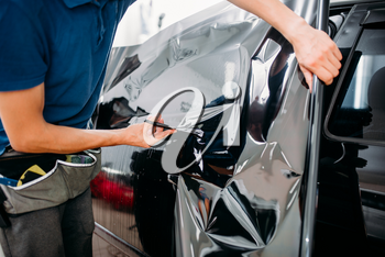 Male specialist with scissors, car tinting film installation process, tinted auto glass installing procedure