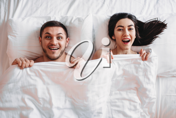 Happy love couple lies on big white bed, top view. Smiling intimate partners in bedroom, hot intimacy lovers