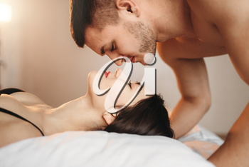 Passionate love couple lies on big white bed, sex romance. Intimate couple in bedroom, intimacy lovers, erotic games