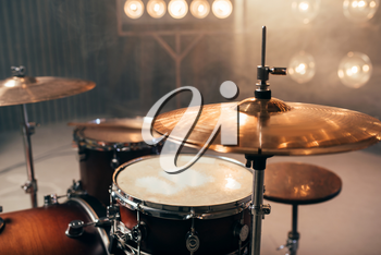 Drum kit, percussion instrument on the stage with lights, nobody. Drummer professional equipment, beat set