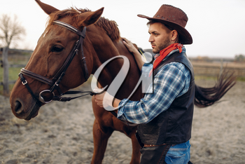 Cowboy in jeans and leather jacket poses with horse on texas ranch, western. Vintage male person with animal, wild west