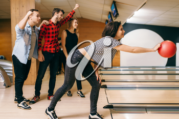 Female bowler on lane, ball throwing in action, strike shot preparation. Bowling alley teams playing the game in club, active leisure