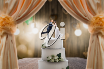 Wedding cake with bride and groom on the top. Pie for newlyweds with little figurines, love symbol