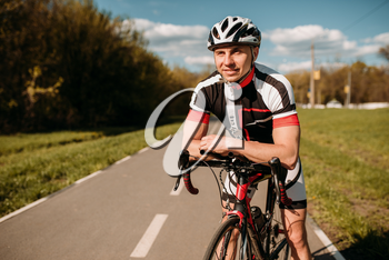 Cyclist in helmet and sportswear, cycling training on asphalt road. Male sportsman rides on bicycle. Workout on bike path