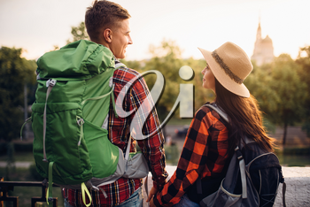 Hikers with backpacks go sightseeing in tourist town on vacation. Summer hiking. Hike adventure of young man and woman