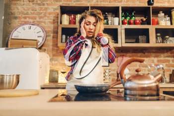 Amazed housewife in an apron looking on frying pan, kitchen interior on background. Female cook prepares fresh homemade cake. Domestic pie preparation