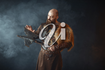Bearded viking dressed in traditional nordic clothes touches the axe blade, barbarian image. Ancient warrior in smoke on dark background
