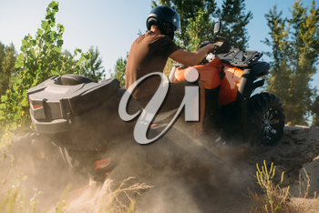 Atv rider climbing the sand mountain in quarry, back view, dust clouds. Male driver in helmet on quad bike, offroad in sandpit