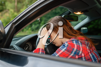 Female driver with blooded face sitting in the car after accident on road. Automobile crash, blood on the woman's face. Broken automobile or damaged vehicle, auto collision on highway