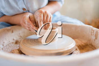 Female potter making a pot on pottery wheel. Woman molding a bowl. Handmade ceramic art, tableware from clay