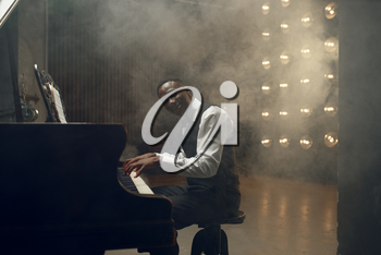 Black grand piano player, jazz performance in club. Black performer poses at musical instrument before playing melody