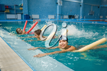 Children swimming group lies on back, workout in the pool. Kids learns to swim in the water, sport training, exercise with board