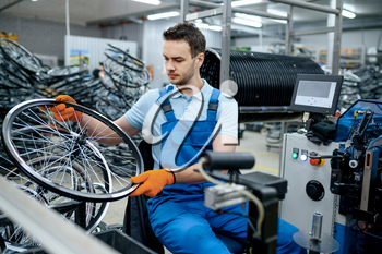 Mechanic in uniform works with bicycle wheel on factory. Bike rims and spokes assembly in workshop, cycle parts installation