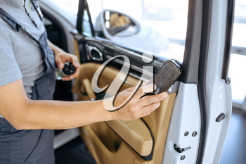 Worker with brush wipes car door trim, dry cleaning and detailing. Vehicle washing in garage, thoroughly care of automobile, chemical and vacuum clean service