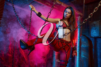 Hot sexy girl in bdsm suit holding on to chains, abandoned factory interior on background. Young girl in erotic underwear, sex fetish, sexual fantasy