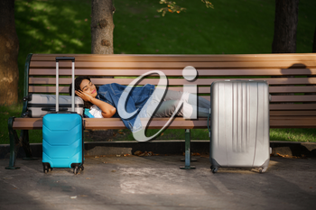 Young woman with suitcase sleeping on the bench in park. Female traveler with luggage leisures outdoors, passenger with bag resting in nature. Girl with baggage relax on city alley