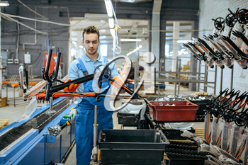 Bicycle factory, worker holds black teen bike frame. Male mechanic in uniform installs cycle parts, assembly line in workshop, industrial manufacturing