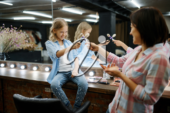 Mother and daughter in salon, makeup artists. Mom and little girl play stylists together, happy childhood, glamour family