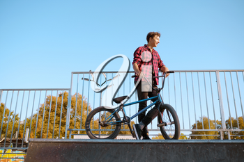 Bmx biker doing trick,teenager on training in skatepark. Extreme bicycle sport, dangerous cycle exercise, risk street riding, biking in summer park