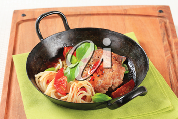 Pan fried meat patty with tomatoes and spaghetti