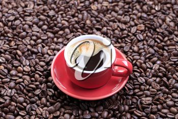 Cup of black coffee on a bed of coffee beans