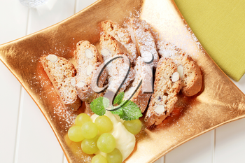 Traditional Italian almond biscotti with grapes and pudding