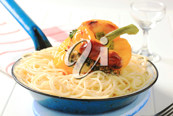 Yellow bell pepper stuffed with ground meat on bed of spaghetti