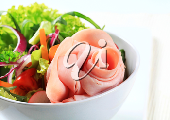 Fresh salad with slices of ham arranged into a rose