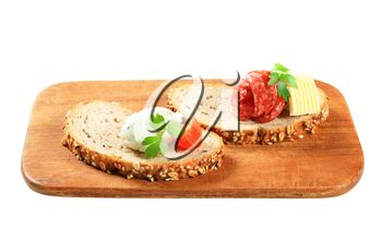 Slices of bread with cheese spread and salami