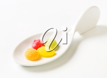 Fruit-shaped gummy candy on ceramic spoon