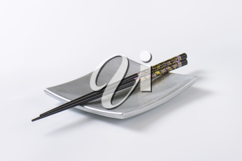 A pair of black chopsticks on empty square silver sushi plate