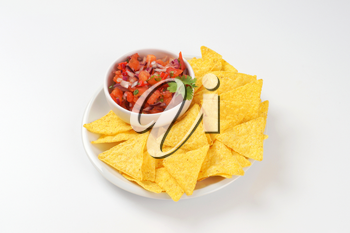 bowl of salsa fresca and tortilla chips on white plate