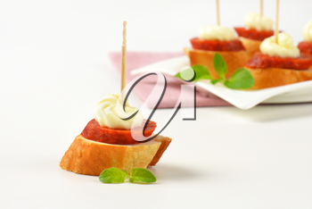 Bread based canapes with spicy sausage and creamy spread