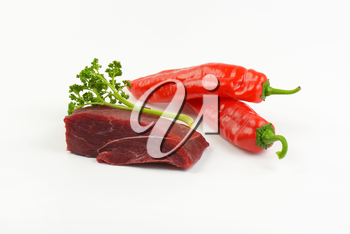 raw beef rump, fresh parsley and red peppers on white background