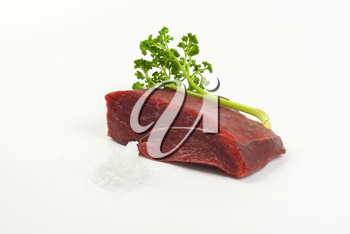 raw beef meat, salt and fresh parsley on white background