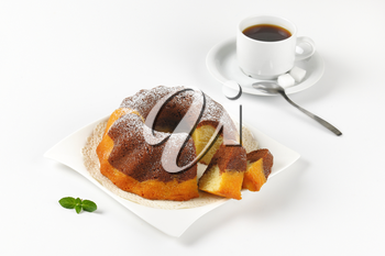 marble bundt cake and cup of black coffee on white background