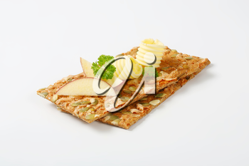 two butter curls and apple slices on pumpkin seed crackers