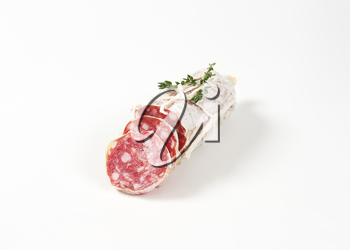 sliced dry cured sausage and thyme on white background
