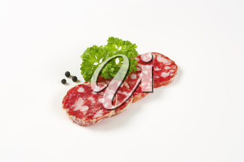 thin slices of dry cured sausage on white background